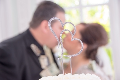 Groom and Bride Out of Focus and Kissing Behind Cake Top